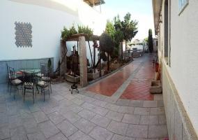 Galería exterior a la vivienda con menaje de jardín