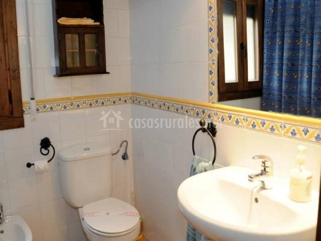 Aseo con azulejos blancos y cenefa amarilla