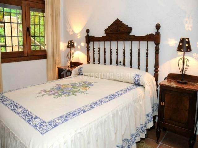 Dormitorio con cama blanca y paredes del mismo color