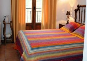 Dormitorio con colcha de colores en la cama