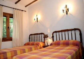Dormitorio con paredes blancas y dos camas