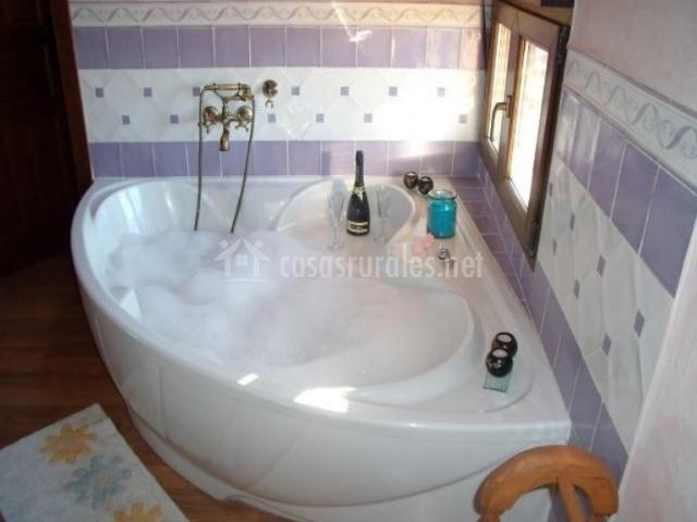 Bañera con azulejos morados y blancos