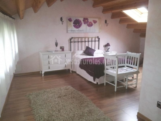 Dormitorio abuhardillado con cama doble