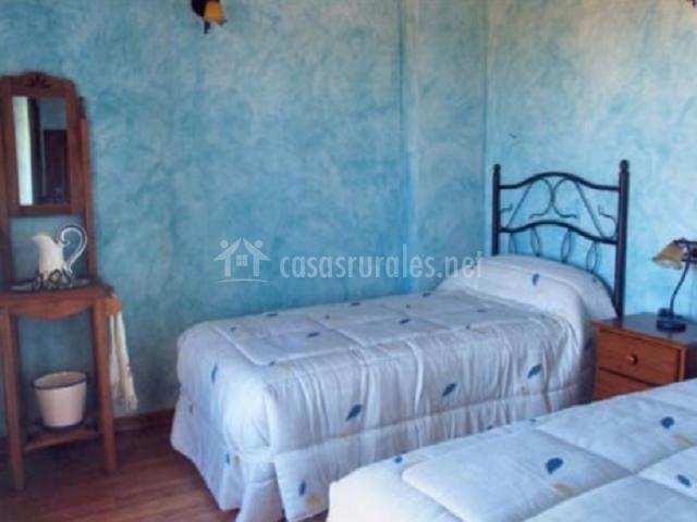 Dormitorio azul con dos camas separadas