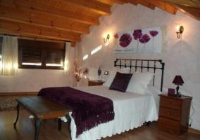 Dormitorio con cama de matrimonio y abuhardillado