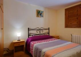 Dormitorio de matrimonio con colcha colorida y mesillas