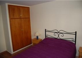 Dormitorio de matrimonio con colcha en morado y armario de madera