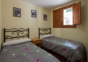 Dormitorio doble con camas individuales y mesilla en el medio