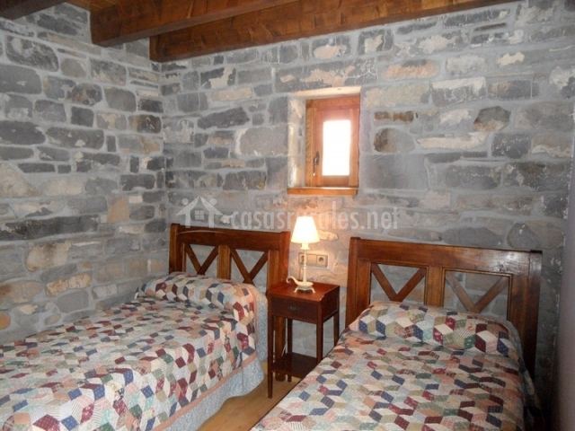 Dormitorio con paredes de piedra y dos camas
