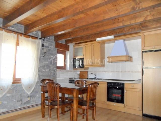 Mesa de comedor y cocina abierta con microondas