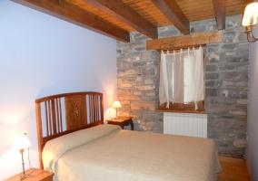 Dormitorio de matrimonio con pared de piedras