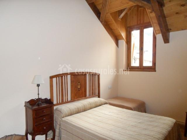 Dormitorio con techo abuhardillado y cama doble