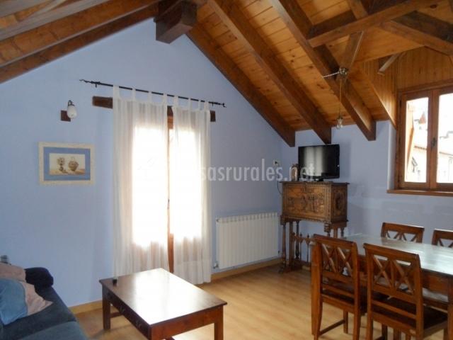Sala de estar con televisor y techo a dos aguas