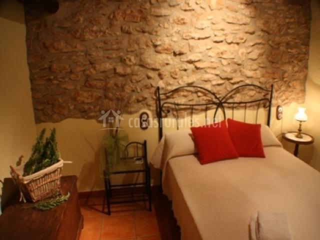 Dormitorio con cama de matrimonio y piedra de fondo