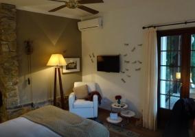 Dormitorio con cama blanca doble y acceso al aseo