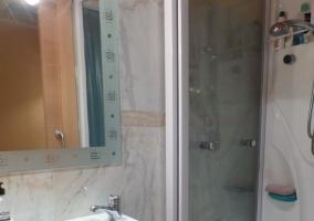 Aseo con ducha y azulejos en blanco y gris
