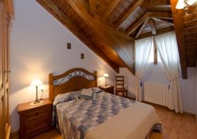Sala de estar con sofá cama y techo abuhardillado