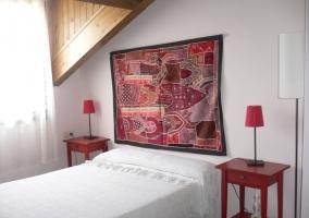 Dormitorio de matrimonio con adorno en la pared