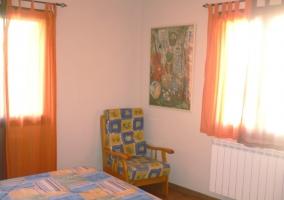 Dormitorio con butaca y cama doble