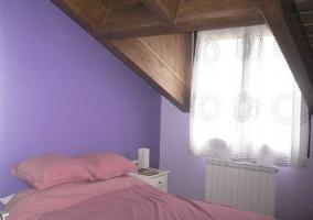 Dormitorio doble abuhardillado con paredes moradas