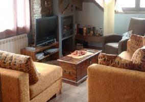 Sala de estar con televisor junto a la chimenea