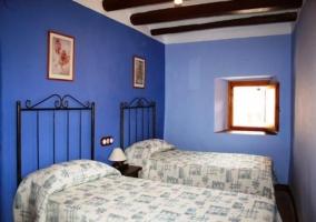 Dormitorio azul con cama doble y una sencilla