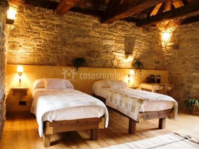 Dormitorio con dos camas individuales pared de piedra