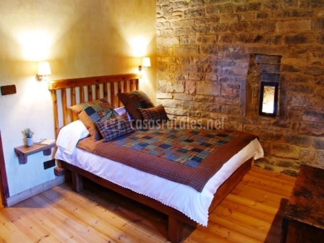 Dormitorio doble con pared de piedra y suelo de madera