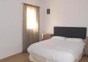 Dormitorio de matrimonio con amplia cama y cabecero de capitoné