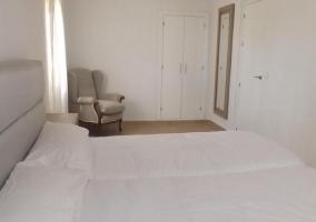 Dormitorio doble con camas individuales en espacio donde predomina el blanco