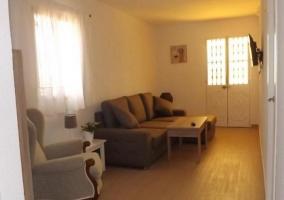 Sala de estar en tonos claros y televisor de plasma