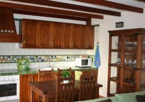 Sala de estar con sillones verdes junto a la escalera de madera