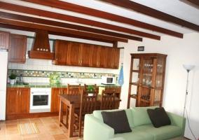 Cocina con muebles de madera y mesa que comunica con la sala de estar