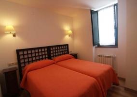 Dormitorio blanco con dos camas naranjas juntas