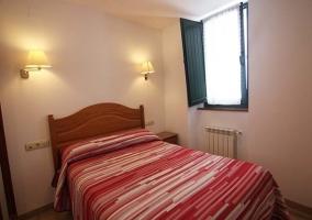 Dormitorio con colcha blanca y roja en la cama