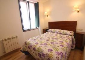 Dormitorio con colcha estampada en la cama y dos mesillas