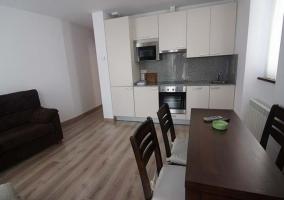 Sala blanca con mesa de comedor y cocina abierta