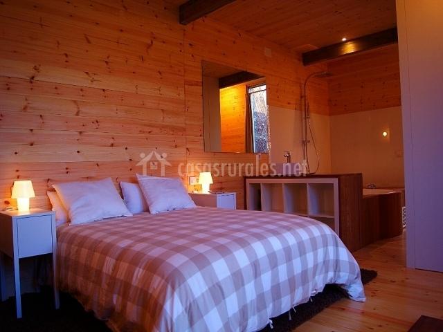 Dormitorio con cama doble y acceso al aseo