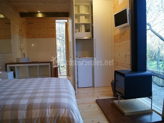 Dormitorio con cama doble y chimenea delante