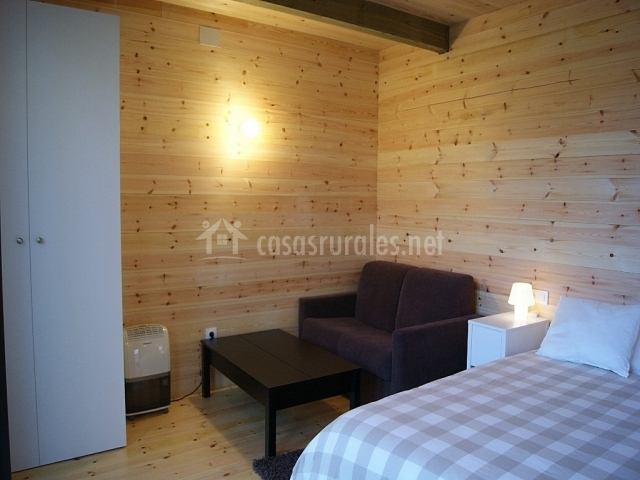 Dormitorio y salita de estar con paredes de madera