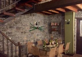 Comedor de la casa con mesa de cristal junto a las escaleras