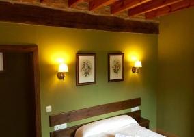 Dormitorio de matrimonio con paredes en verde y techos de madera