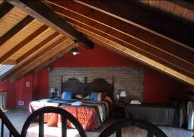 Dormitorio triple abuhardillado con paredes en tonos rojos