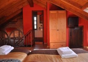 Dormitorio triple abuhardillado en tonos rojizos