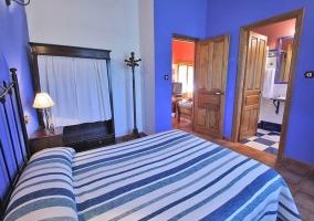 Dormitorio azulado con cama de matrimonio