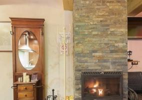 Sala de estar con chimenea y cocina con armarios de madera