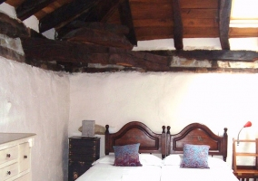 Camas individuales bajo techos de madera
