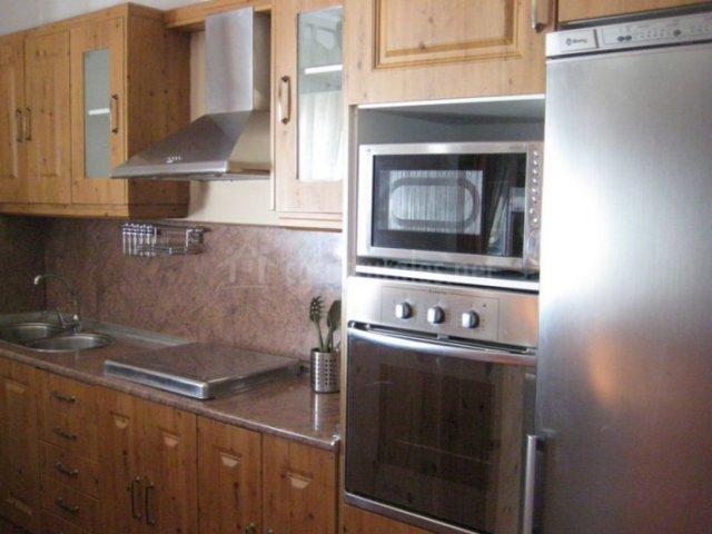 Cocina con electrodomésticos de acero y armarios de madera