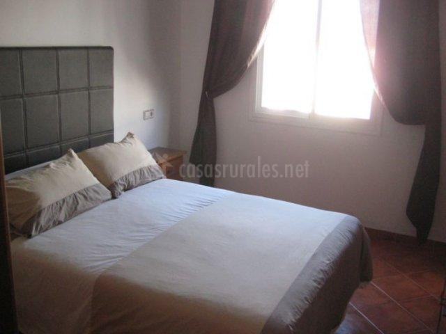Dormitorio con ventana en un lateral y cama en tonos crema