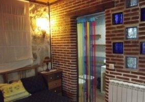 Dormitorio con pared de ladrillo y aseo privado